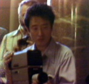 Nam Jun Paik at the camera during a performance of the TV Cello. (video still from photograph: Stephen Jones)