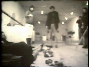Still from Sequence 11 of Idea Demonstrations. Six spectators lie on the floor. Their shoes are removed and tied to a string which is then raised and dropped.