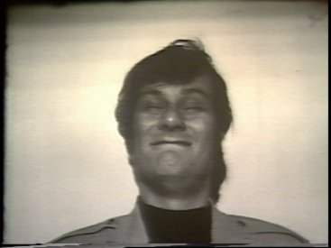 Still from Sequence 14 of Idea Demonstrations. Mike Parr stares into a bright light until he blinks.